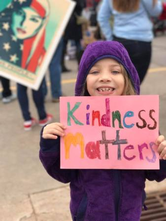"Young girl at Women's March (2017) holding a sign she made that reads ""kindness matters"""